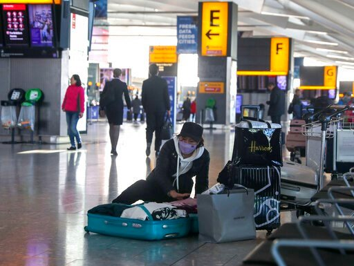 (Steve Parsons/PA via AP). A woman wearing a face mask packs her suitcase in the departures area of Terminal 5, after it was announced British Airways has suspended all services to and from China, at London's Heathrow Airport, Wednesday, Jan. 29, 2020....