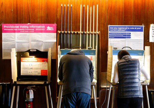 (AP Photo/Charles Rex Arbogast, File). FILE - In this Nov. 8, 2016, file photo, residents of Chicago' 33rd Ward mark their ballots at Marie's Golden Cue pool hall. An embarrassing mistake in Illinois' automatic voter registration system could mean depo...