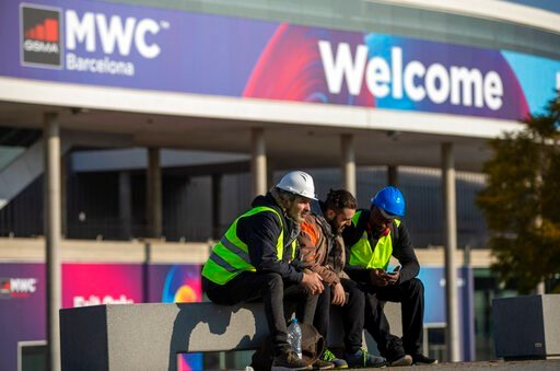 (AP Photo/Emilio Morenatti). Workers at the Mobile World Congress sit outside the venue in Barcelona, Spain, Thursday, Feb. 13, 2020. Organizers of the world's biggest mobile technology fair are pulling the plug over worries about the viral outbreak fr...