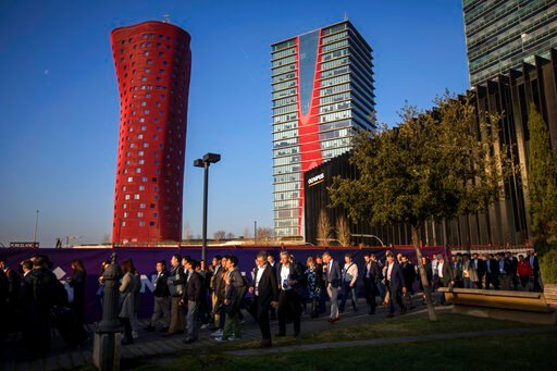 (AP Photo/Emilio Morenatti). In this Feb. 25, 2019 photo, attendees walk to enter at the Mobile World Congress wireless show, in Barcelona, Spain. Organizers of the world's biggest mobile technology fair are pulling the plug over worries about the vira...
