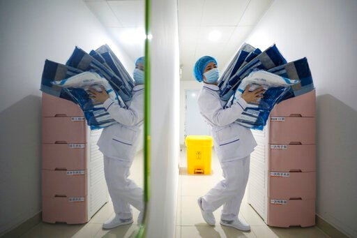 (Chinatopix Via AP). A worker prepares medical supplies at the Jinyintan Hospital, designated for critical COVID-19 patients, in Wuhan in central China's Hubei province Thursday, Feb. 13, 2020. China on Thursday reported 254 new deaths and a spike in v...