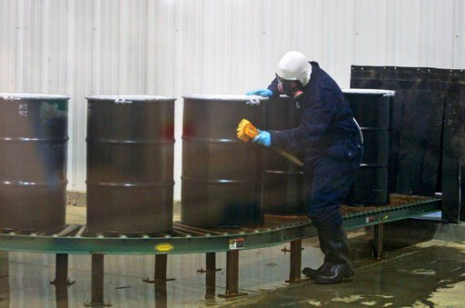 (Alan Rogers/The Casper Star-Tribune via AP, File). FILE - In this Monday, Dec. 9, 2013, file photo, a worker decontaminates steel drums containing yellowcake uranium to ensure safe shipment at UR Energy's Lost Creek uranium production facility in Swee...