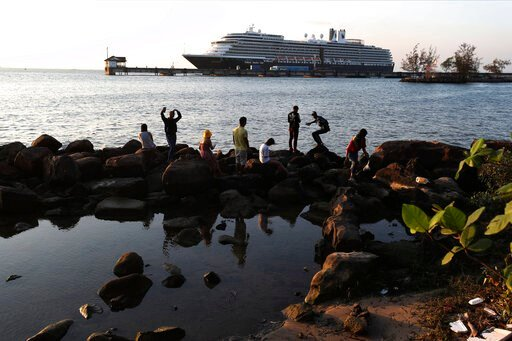 (AP Photo/Heng Sinith). Locals come down to view the Westerdam cruise ship, owned by Holland America Line, docked at the port of Sihanoukville, Cambodia, Thursday, Feb. 13, 2020. The Westerdam, turned away by four Asian and Pacific governments due to v...