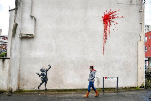(Ben Birchall/PA via AP). A woman walks past a new artwork on the side of a house in Bristol, England, Thursday Feb. 13, 2020, which has been confirmed as the work of street artist Banksy.