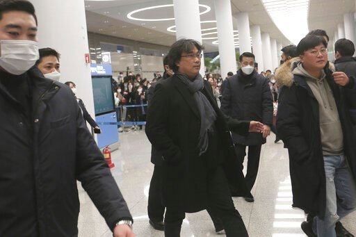 """(AP Photo/Ahn Young-joon). South Korean director Bong Joon-ho, center, arrives at the Incheon International Airport in Incheon, South Korea, Sunday, Feb. 16, 2020. South Koreans are reveling in writer-director Bong's dark comic thriller, """"Parasite,"""" wh..."""