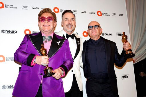 (Photo by Willy Sanjuan/Invision/AP). Elton John, from left, David Furnish, and Bernie Taupin celebrate Elton John and Bernie Taupin winning an Academy Award as they arrive at the 2020 Elton John AIDS Foundation Oscar Viewing Party on Sunday, Feb. 9, 2...
