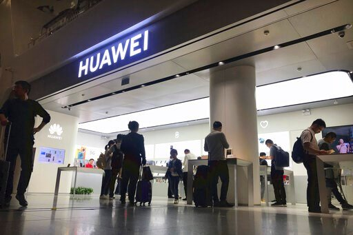 (AP Photo/Olivia Zhang, File). FILE - In this Nov. 15, 2019, file photo people look at a Huawei store in Shenzhen Bao'an International Airport in Shenzhen in southern China's Guangdong Province. A federal judge in Texas has dismissed Chinese tech giant...