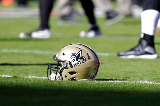 (AP Photo/Jeff Roberson, File). FILE - In this Oct. 23, 2016, file photo, a New Orleans Saints helmet rests on the playing field before an NFL football game in Kansas City, Mo. An Associated Press review of public tax documents found that the Bensons' ...
