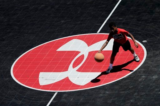 (AP Photo/Julio Cortez, File). FILE - In this July 1, 2019, file photo the logo for Under Armour, which is based in Baltimore, is seen at half court as Neko Coleman, 10, plays basketball during a summer day at Federal Hill Park in Baltimore. Under Armo...