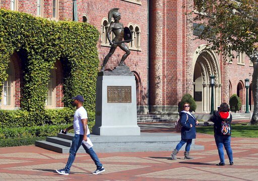 (AP Photo/Reed Saxon, File). FILE - In this March 12, 2019 file photo, people pose for photos in front of the iconic Tommy Trojan statue on the campus of the University of Southern California in Los Angeles. USC will phase in free tuition for students ...