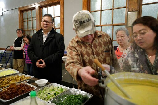 (AP Photo/Steven Senne). In this Sunday, Feb. 16, 2020, photo Baptist Pastor Clifford Maung, third from left, recites a prayer as Chin Sai, center, and Myint Myint Swe, right, prepare food following services at the Overseas Burmese Christian Fellowship...