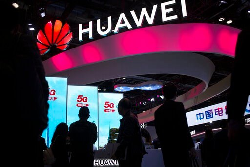 (AP Photo/Mark Schiefelbein, File). FILE - In this Oct. 31, 2019, file photo, attendees walk past a display for 5G services from Chinese technology firm Huawei at the PT Expo in Beijing. The Trump administration is stepping up pressure on European alli...