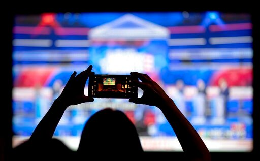 (AP Photo/David Goldman, File). FILE - In this June 27, 2019, file photo, a woman takes a photo of the television while watching a Democratic presidential debate at a watch party in Atlanta. The Democratic race for the White House has been marked by on...