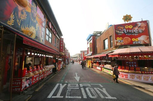 (AP Photo/Ahn Young-joon). In this Feb. 14, 2020, photo, a woman wearing a face mask walks on a almost empty street at the Chinatown in Incheon, South Korea. Even as cases and deaths from the new virus mount, fear is advancing like a tsunami - and not ...