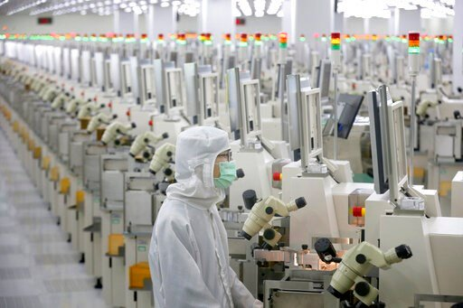 (Chinatopix via AP). In this Feb. 20, 2020, photo, a worker sits at a production line at a microelectronics factory in Nantong in eastern China's Jiangsu Province. China on Friday suspended more punitive tariffs on imports of U.S. industrial goods in r...