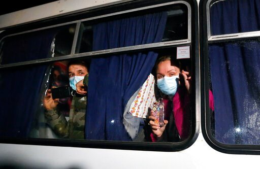 (AP Photo/Efrem Lukatsky). Ukrainian passengers evacuated from the Chinese city of Wuhan, look though a bus window outside Novi Sarzhany, Ukraine, Thursday, Feb. 20, 2020. Several hundred residents in Ukraine's Poltava region protested to stop official...