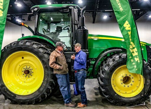 (Greg Eans/The Messenger-Inquirer via AP). Larry Krampe of Rome, Ky, left, talks with Bill Brey of Whitesville, Ky while the two stand next to a John Deere model 8345 R tractor on display inside the Owensboro Convention Center during the 46th annual Ag...
