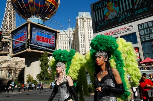 (AP Photo/John Locher, File). FILE - In this Feb. 19, 2020, file photo, people dressed as showgirls walk near the Paris Las Vegas hotel casino, site of a Democratic presidential debate in Las Vegas. Just past the roulette wheel and slot machines, the s...