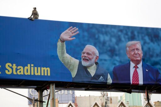 (AP Photo/Ajit Solanki, File). FILE- In this Feb. 19, 2020, file photo, a monkey sits on a hoarding welcoming U.S. President Donald Trump ahead of his visit to Ahmedabad, India. A festive mood has enveloped Ahmedabad in India's northwestern state of Gu...