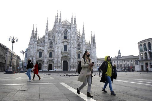 (AP Photo/Luca Bruno). A woman wearing a sanitary mask walks past the Duomo gothic cathedral in Milan, Italy, Sunday, Feb. 23, 2020. A dozen Italian towns saw daily life disrupted after the deaths of two people infected with the virus from China and a ...