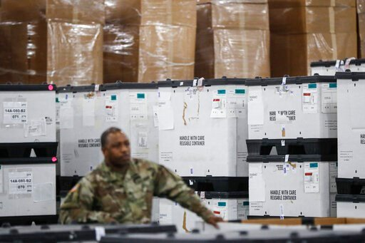 (AP Photo/John Minchillo, File). FILE - In this March 23, 2020, file photo, a U.S. National Guard member stands beside crates of medical supplies at the Jacob Javits Center, in New York. The use of National Guard units around the country to help with t...