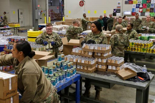 (AP Photo/Tony Dejak, File). FILE - In this March 24, 2020, file photo, members of The Ohio National Guard assist in repackaging emergency food boxes for food distribution at the Cleveland Food Bank in Cleveland. The use of National Guard units around ...