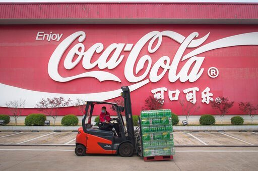 (Xiao Yijiu/Xinhua via AP). In this Tuesday, March 24, 2020, photo released by China's Xinhua News Agency, a worker wearing a face mask drives a forklift at a Swire Coca-Cola Beverages Hubei Limited plant in Wuhan in central China's Hubei Province. Acc...