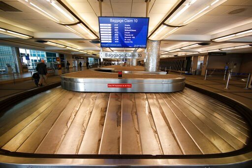 (AP Photo/David Zalubowski, File). FILE - In this March 20, 2020 file photo, an empty baggage carousel spins in Denver International Airport as travelers deal with the spread of the coronavirus  in Denver.  Airline service in the United States is teete...
