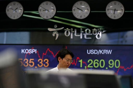 (AP Photo/Lee Jin-man). A currency trader walks by screens showing the Korea Composite Stock Price Index (KOSPI), left, and the foreign exchange rate between U.S. dollar and South Korean won at the foreign exchange dealing room in Seoul, South Korea, T...