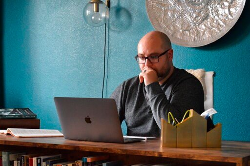 (Brett Seidl via AP). In this photo provided by Brett Seidl, Jonathon Seidl sits in his home office in Dallas on Wednesday, March 18, 2020. He said he wasn't worried about the coronavirus despite his anxiety disorder. But that changed. The 33-year-old ...
