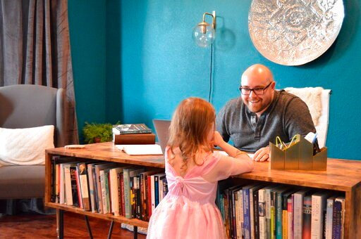 (Brett Seidl via AP). In this photo provided by Brett Seidl, Jonathon Seidl talks with his daughter in his home office in Dallas on Wednesday, March 18, 2020. He said he wasn't worried about the coronavirus despite his anxiety disorder. But that change...