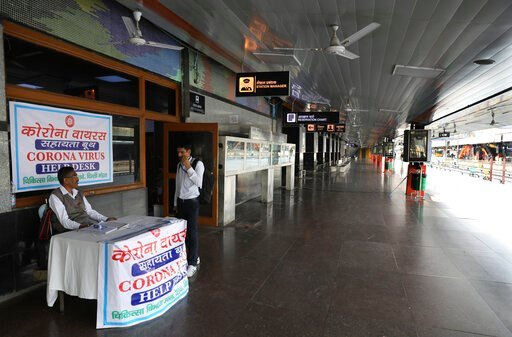 (AP Photo/Manish Swarup). FILE- In this Monday, March 23, 2020, file photo, an Indian railways employee sits at a coronavirus help desk at the deserted New Delhi Railway station during a lockdown amid concerns over the spread of Coronavirus, in New Del...