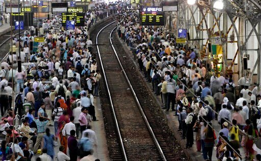 (AP Photo/Rajanish Kakade, File). FILE - In this Wednesday, July 11, 2012, file photo, Indian commuters wait for trains at the Churchgate railway station in Mumbai, India. India's colossal passenger railway system has come to a halt Sunday, March 22, 2...