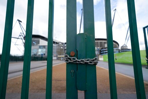 (AP Photo/Jon Super). A locked gate is seen by the Etihad Stadium where Manchester City was due to play Burnley in an English Premier League soccer match Saturday March 14, 2020, after all English soccer games were cancelled due to the spread of the CO...