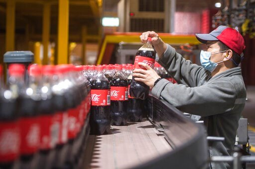 (Xiao Yijiu/Xinhua via AP). This Tuesday, March 24, 2020, photo released by China's Xinhua News Agency, shows a worker wearing a face mask on a production line at a Swire Coca-Cola Beverages Hubei Limited plant in Wuhan in central China's Hubei Provinc...