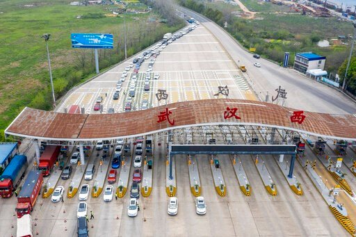 (Cai Yang/Xinhua via AP). In this March 24, 2020, photo released by Xinhua News Agency, an aerial photo shows vehicles waiting to cross into Wuhan at a highway toll station in Wuhan, in central China's Hubei Province. Hubei has ended a lockdown for mos...