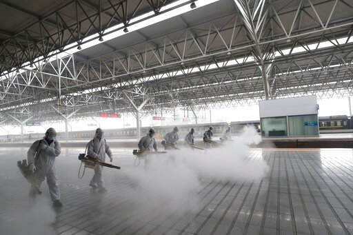 (Photo by Wang Shen/Xinhua). In this March 24, 2020, photo released by Xinhua News Agency, firefighters conduct disinfection on the platform at Yichang East Railway Station in Yichang, in central China's Hubei Province, March 24, 2020. China is re-open...