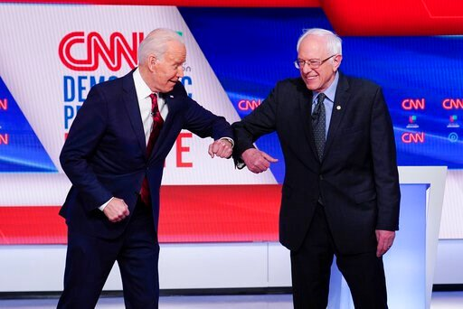 (AP Photo/Evan Vucci). Former Vice President Joe Biden, left, and Sen. Bernie Sanders, I-Vt., right, greet one another before they participate in a Democratic presidential primary debate at CNN Studios in Washington, Sunday, March 15, 2020.