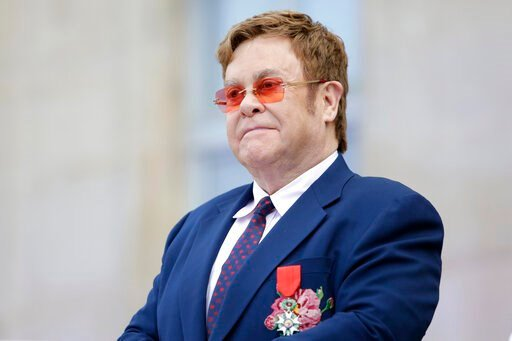 "(AP Photo/Lewis Joly, Pool, File). FILE - This June 21, 2019 file photo shows Elton John at a ceremony honoring him with the Legion of Honor in Paris. John is hosting a ""living room"" concert aimed at bolstering American spirits during the coronavirus c..."