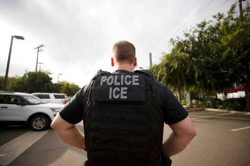 (AP Photo/Gregory Bull, File). FILE - In this July 8, 2019, file photo, a U.S. Immigration and Customs Enforcement (ICE) officer looks on during an operation in Escondido, Calif.  Pressure is mounting on the Trump administration to release people from ...