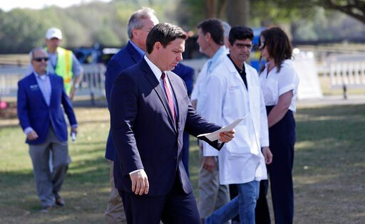 (AP Photo/John Raoux, File). FILE- In this March 23, 20202 file photo, Florida Gov. Ron DeSantis, center front, arrives at a mobile testing site for a press conference Monday, March 23, 2020, in The Villages, Fla. The Villages, a retirement community, ...