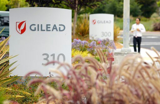 (AP Photo/Eric Risberg, File). FILE - In this July 9, 2015, file photo, a man walks outside the headquarters of Gilead Sciences in Foster City, Calif. Gilead Sciences said Wednesday, March 25, 2020 it will give up the specialty status it received days ...