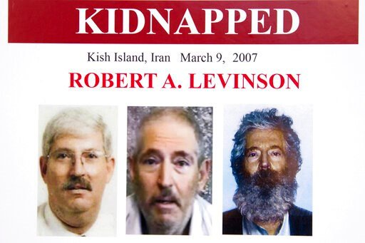 (AP Photo/Manuel Balce Ceneta, File). FILE - In this March 6, 2012, file photo, an FBI poster showing a composite image of former FBI agent Robert Levinson, right, of how he would look like now after five years in captivity, and an image, center, taken...