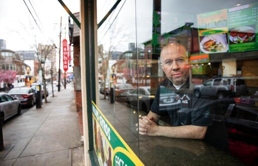 """(AP Photo/David Goldman). Paul Boutros, owner of East Side Pockets, a small restaurant near Brown University, looks out onto an empty street since students were sent home two weeks ago, Wednesday, March 25, 2020, in Providence, R.I. """"He's not being rea..."""