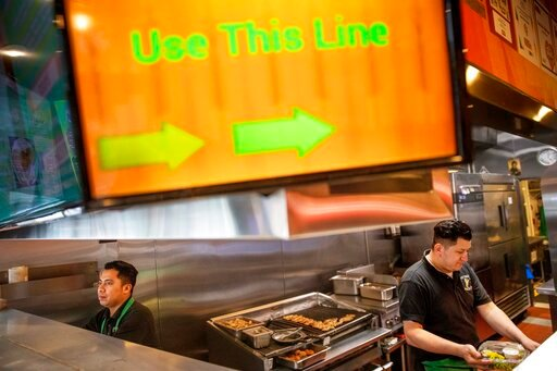 (AP Photo/David Goldman). Carlos Gutierrez, left, and Marcos Morales prepare take-out orders at East Side Pockets, a small restaurant near Brown University, Wednesday, March 25, 2020, in Providence, R.I. While Trump is anxious to get the economy moving...