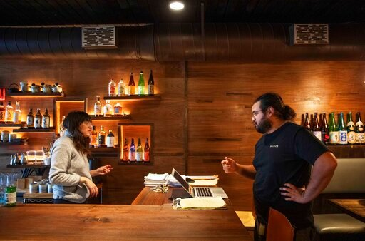 (AP Photo/David Goldman). James Mark, right, owner of the restaurant Big King, talks with Jennifer Wittlin as they prepare for dinner take-out orders Wednesday, March 25, 2020, in Providence, R.I. Mark said pushing to restart the economy before the hea...