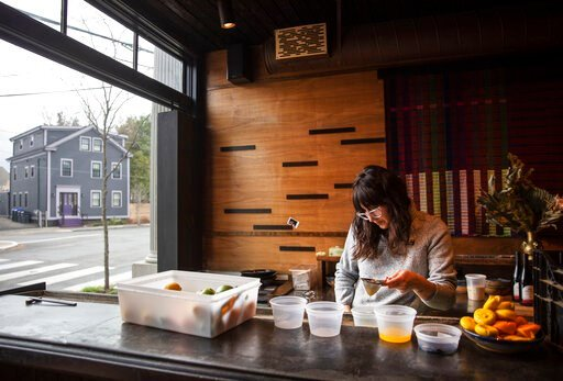 (AP Photo/David Goldman). Jennifer Wittlin prepares for dinner take-out orders at Big King on terriWednesday, March 25, 2020, in Providence, R.I. Owner James Mark said pushing to restart the economy before the health crisis is over would put businesses...