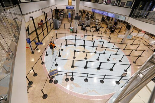 (AP Photo/Rick Bowmer). A traveler walks through the security line at the Salt Lake City International Airport Wednesday, March 25, 2020, in Salt Lake City. Many airline flights are nearly empty as virus undercuts travel. The Salt Lake City Internation...