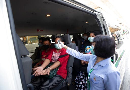 (AP Photo/Sakchai Lalit). Health officer check temperature passenger in van at a health check point in Bangkok, Thailand, Thursday, March 26, 2020. It is the first day of month long state of emergency enforced in Thailand to allow its government to imp...