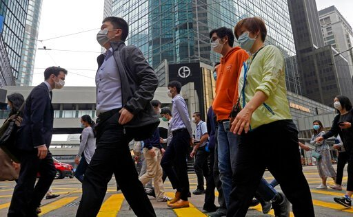 (AP Photo/Vincent Yu). People wearing face masks walk at a downtown street in Hong Kong Thursday, March 26, 2020. For most, the coronavirus causes only mild or moderate symptoms, such as fever and cough. But for a few, especially older adults and peopl...